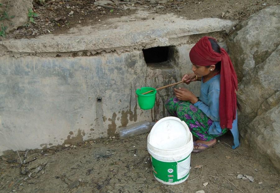 बझाङ्गीमा परम्परागत कुवाको पानी भर्दै बालिका
